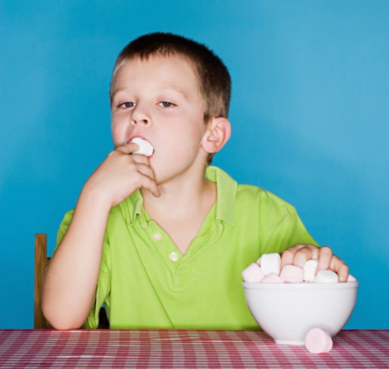 Мальчик ест зефир